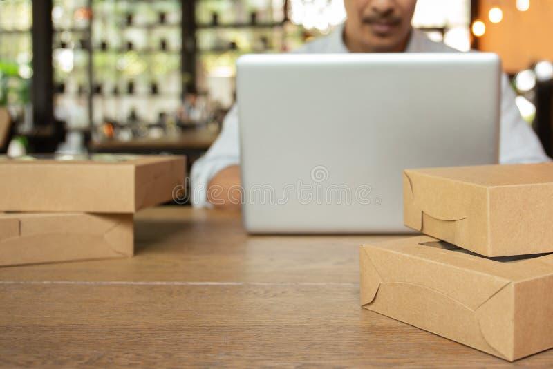Startgeschäftsmann, der an Computerlaptop mit Paket auf Tabelle arbeitet stockfoto