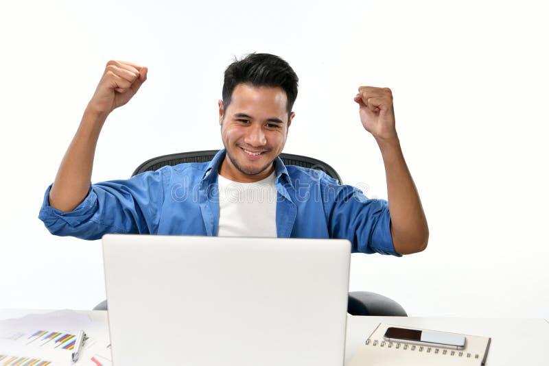 Startgeschäftsmann, der seine Hände sich fühlen glücklich für das Erzielen der Arbeit bei der Anwendung des Laptops anhebt stockfoto