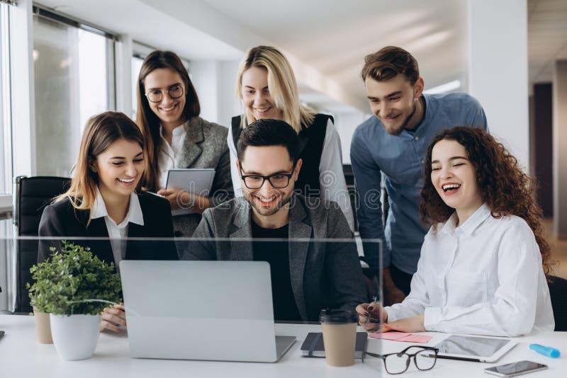 Startgeschäftsteam auf dem Treffen im modernen hellen Büroinnenraum lächelnd und an Laptop arbeitend stockfotografie