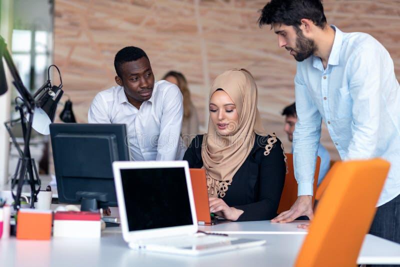 Startgeschäftsteam auf Sitzung im Innenbrainstorming des modernen hellen Büros, in der Funktion auf Laptop und im Tablet-Computer lizenzfreie stockfotografie
