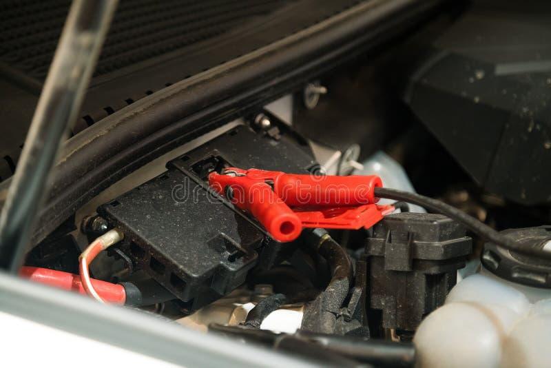 Starthilfekabel befestigt unter Autohaube, um zu helfen, Automotor anzulassen Reparaturwerkstatt lizenzfreies stockbild