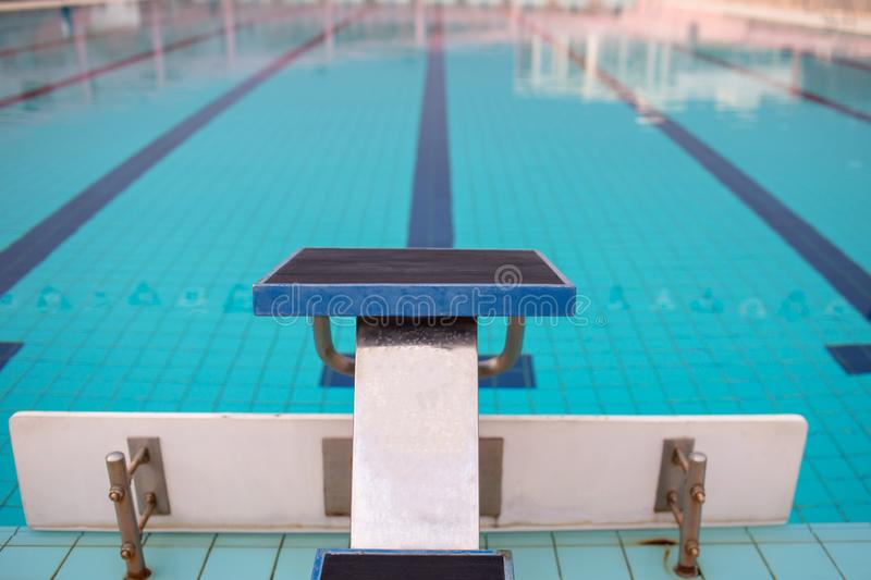 Starting blocks in row by the swimming pool, selective focus. Jump platform for swimming in swimming pool and grandstand backgroun. D. Swimming pool with stock photo
