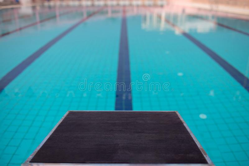 Starting blocks in row by the swimming pool, selective focus. Jump platform for swimming in swimming pool and grandstand backgroun. D. Swimming pool with royalty free stock photo