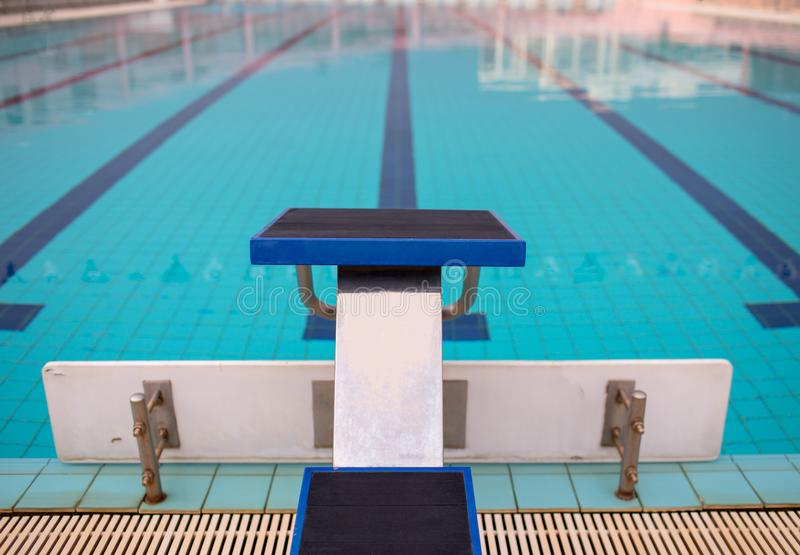 Starting blocks in row by the swimming pool, selective focus. Jump platform for swimming in swimming pool and grandstand backgroun. D. Swimming pool with royalty free stock photos