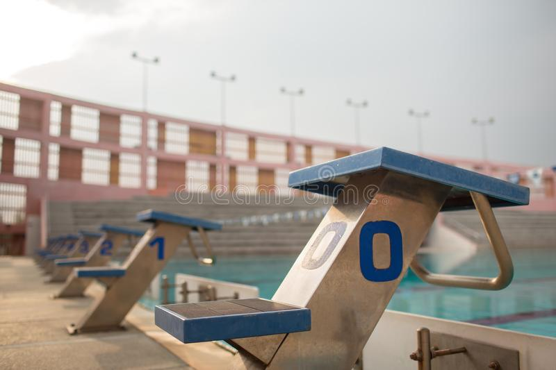 Starting blocks in row by the swimming pool, selective focus. Jump platform for swimming in swimming pool and grandstand backgroun. D. Swimming pool with stock photography