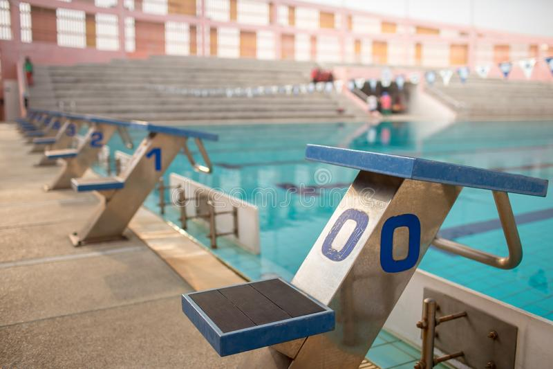 Starting blocks in row by the swimming pool, selective focus. Jump platform for swimming in swimming pool and grandstand backgroun. D. Swimming pool with stock image