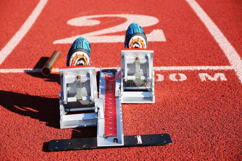 Starting blocks with spikes and a baton. Starting blocks in lane 2 with spikes set in them and a baton for a relay race stock photo