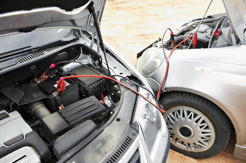 Starting car engine with battery jumper cables royalty free stock images