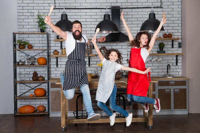 Starting day. Happy family in kitchen. Mother and father with little girl. Family day. Little girl with parents. Father. Mother and child chef. Little girl stock image