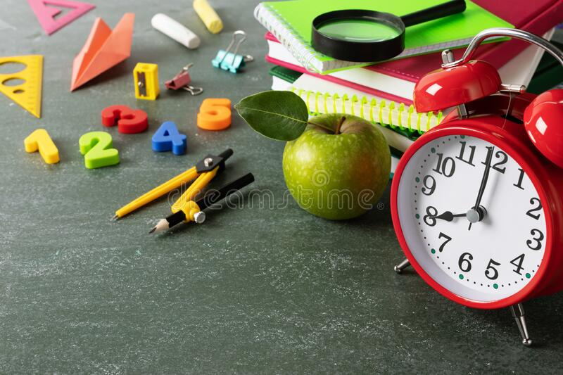 Starting education or back to school concept with red alarm clock, fresh green apple and colorful school supplies on blackboard stock photography