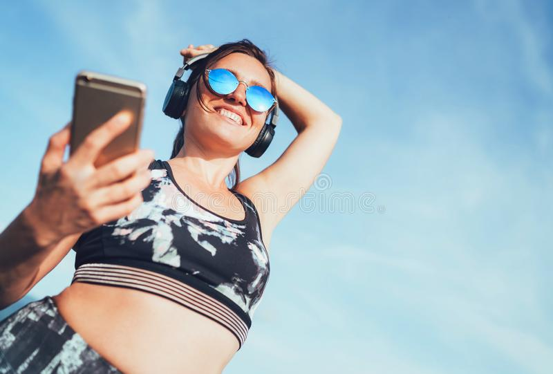 Starting her run training with music. Positive middle-aged beautiful woman jogging and listening to music using smartphone and. Wireless headphones cheerfully royalty free stock photography