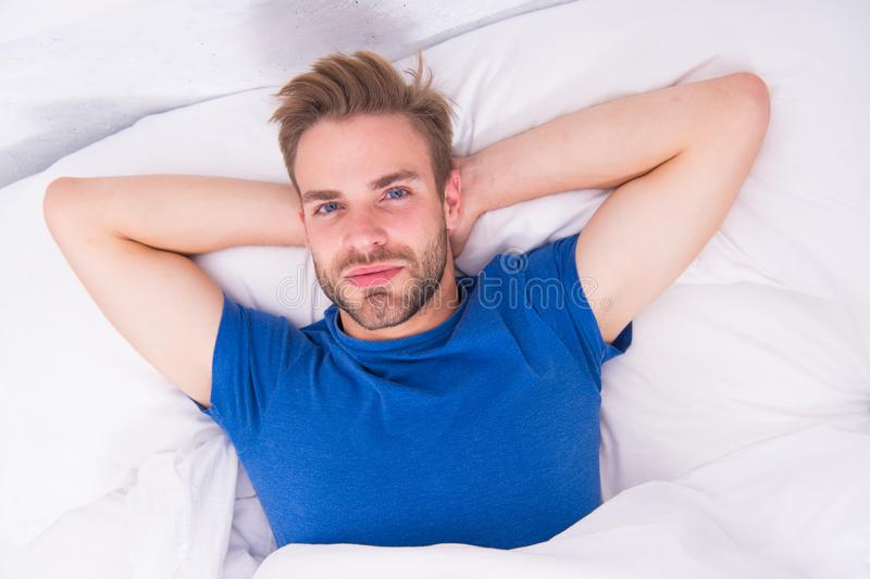 Starting his day with regular routine. Handsome guy awaken for morning routine. Sexy man lying in bed before grooming stock images