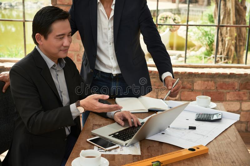 Starting new business. Smiling entrepreneures showing e-mail on laptop screen to coworker royalty free stock photo