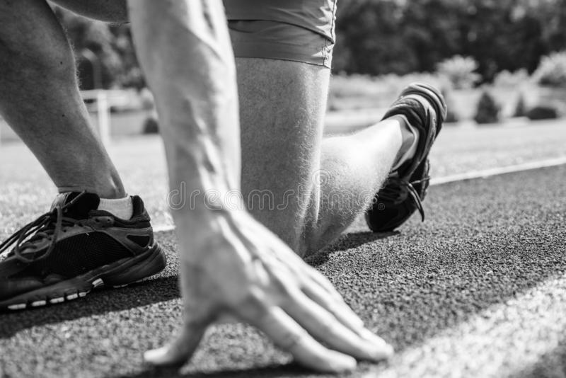 Starting point. Hand of sportsman on running track low start position. Runner ready to go close up. Ready steady go. Concept. At the beginning of great sport royalty free stock photography