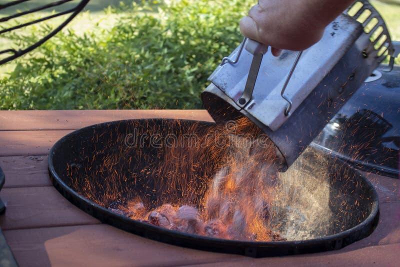 Startknapp för brand för Bbq-lampglaskol mycket av brinnande briketter som dumpas in i ett utomhus- galler med gnistaflyg arkivfoto