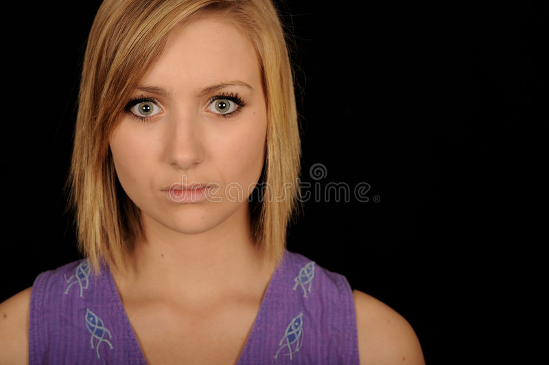 Startled Teenager. A portrait of a beautiful teenage girl with a startled expression on her face, on black studio background royalty free stock photo