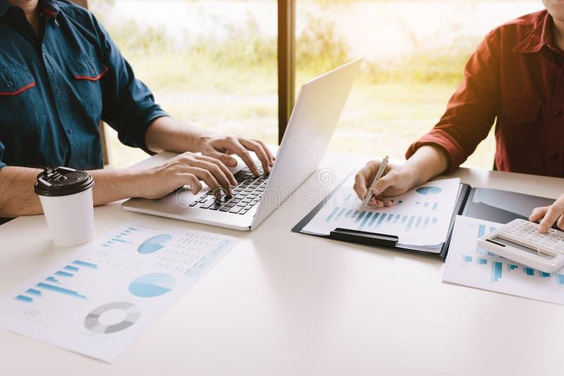 Startleute, die zusammen am Büroraumtisch und an balancierendem Budget sitzen stockfotografie