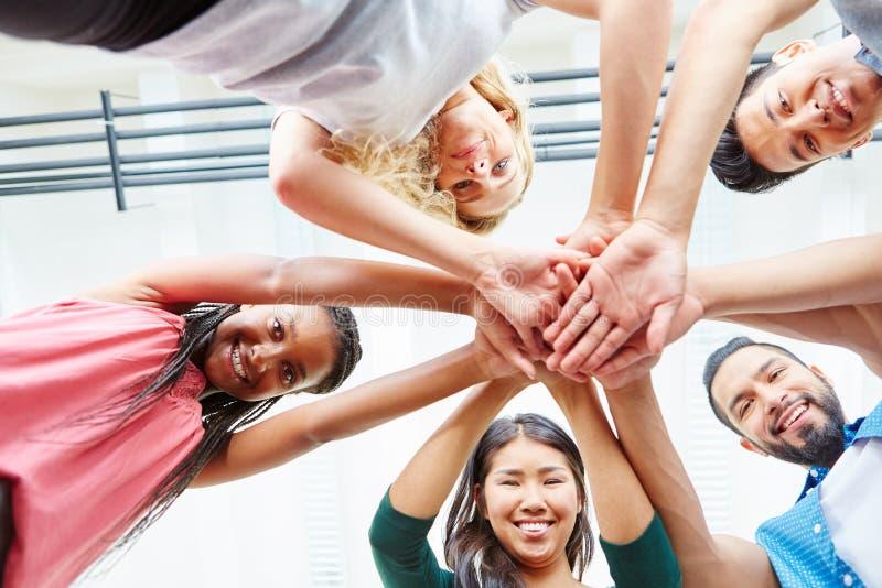 Startstudenten, die zusammen ihre Hände stapeln lizenzfreie stockfotografie