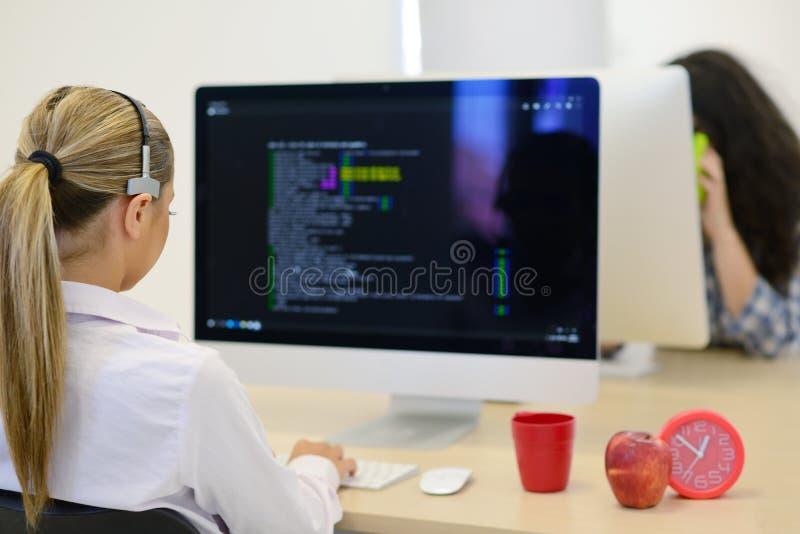 Startup affär, ung kvinna som programvarubärare som arbetar på datoren på det moderna kontoret arkivfoton