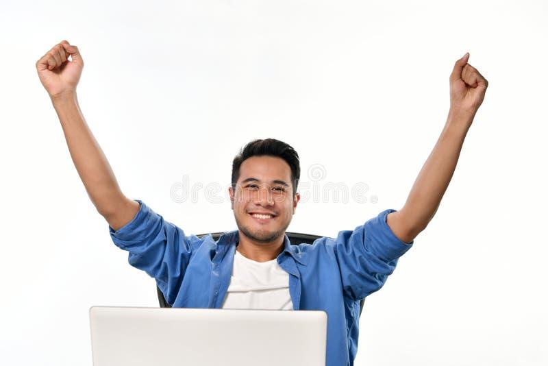 Startup affärsman som lyfter hans händer som känner sig lyckliga för att uppnå arbete, medan genom att använda bärbara datorn arkivbilder