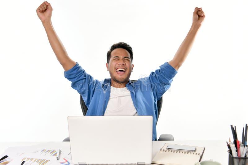 Startup affärsman som lyfter hans händer som känner sig lyckliga för att uppnå arbete, medan genom att använda bärbara datorn royaltyfri foto