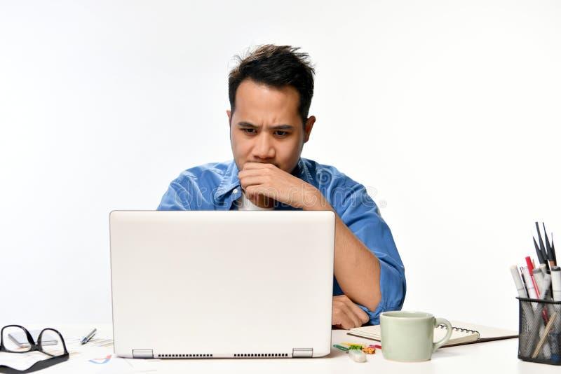 Startup affärsman som täcker hans mun med hans hand som ser spänd, medan genom att använda en bärbar dator royaltyfri fotografi