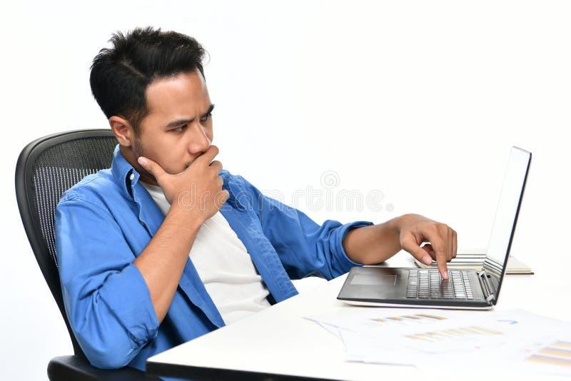Startup affärsman som täcker hans mun med hans hand som ser spänd, medan genom att använda en bärbar dator royaltyfri bild