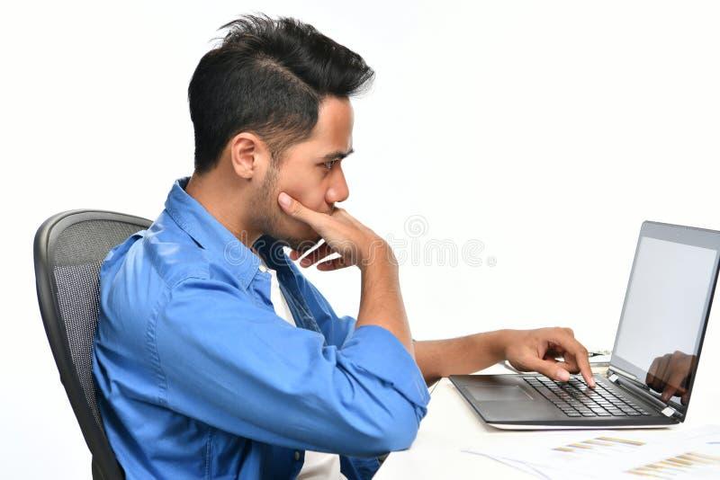Startup affärsman som täcker hans mun med hans hand som ser spänd, medan genom att använda en bärbar dator arkivbild