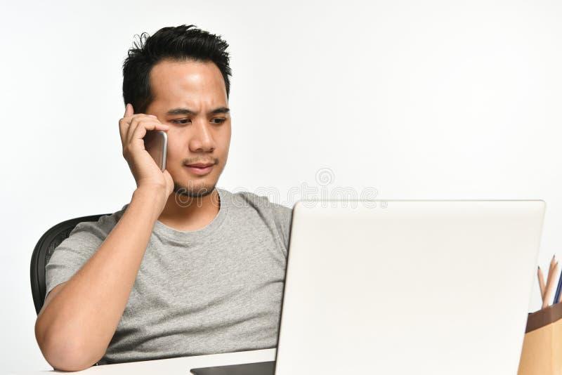 Startup affärsman som talar på telefonen och använder bärbara datorn arkivbild