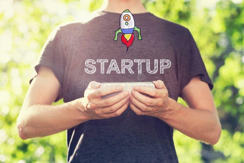 Startup begrepp med den unga mannen som utanför rymmer hans smartphone royaltyfria bilder