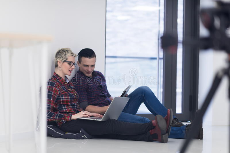 Startup business, couple working on laptop computer at office. Startup business and new mobile technology concept with young couple in modern bright office royalty free stock photo