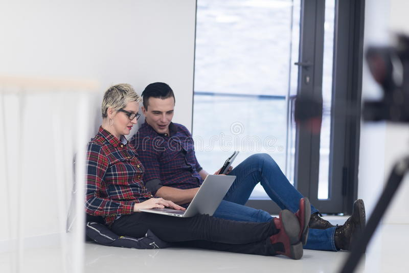 Startup business, couple working on laptop computer at office. Startup business and new mobile technology concept with young couple in modern bright office royalty free stock photos