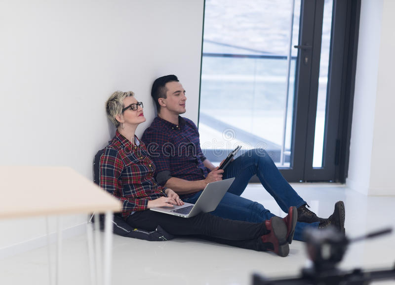Startup business, couple working on laptop computer at office. Startup business and new mobile technology concept with young couple in modern bright office stock images