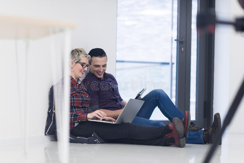 Startup business, couple working on laptop computer at office. Startup business and new mobile technology concept with young couple in modern bright office stock image