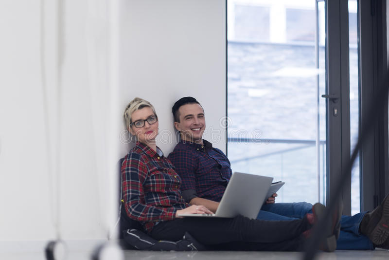 Startup business, couple working on laptop computer at office. Startup business and new mobile technology concept with young couple in modern bright office royalty free stock image