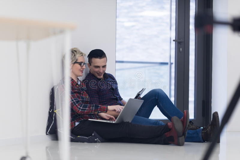 Startup business, couple working on laptop computer at office. Startup business and new mobile technology concept with young couple in modern bright office stock photography