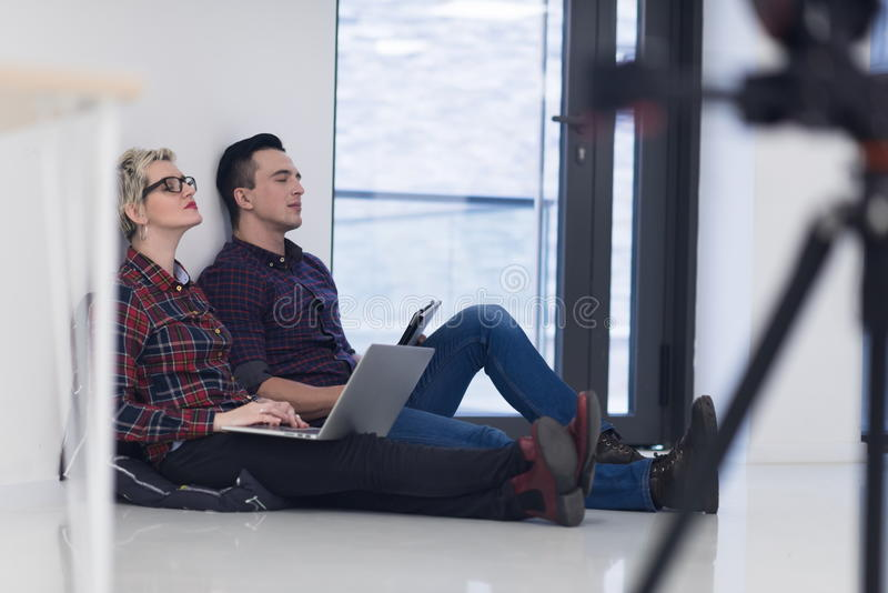 Startup business, couple working on laptop computer at office. Startup business and new mobile technology concept with young couple in modern bright office royalty free stock images