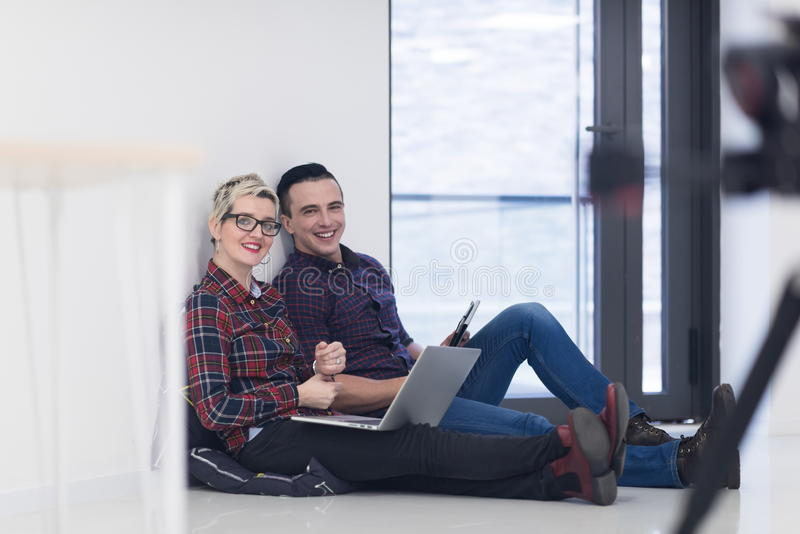 Startup business, couple working on laptop computer at office. Startup business and new mobile technology concept with young couple in modern bright office stock photo