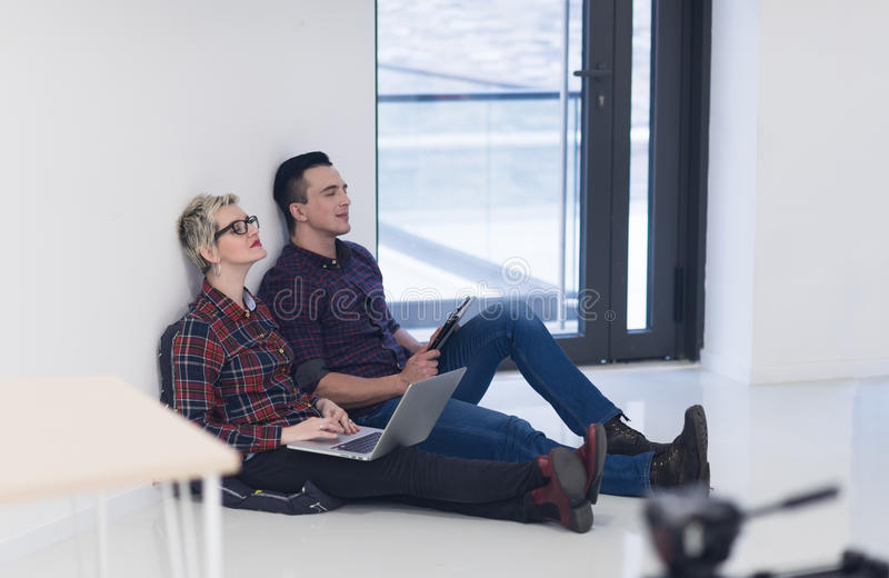 Startup business, couple working on laptop computer at office. Startup business and new mobile technology concept with young couple in modern bright office royalty free stock photography
