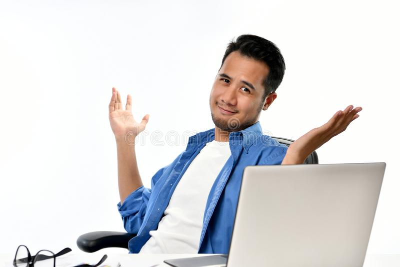 Startup business man sitting in relaxed posture with hands raised after having work done easily. Casually-dressed startup business man sitting in relaxed posture stock image