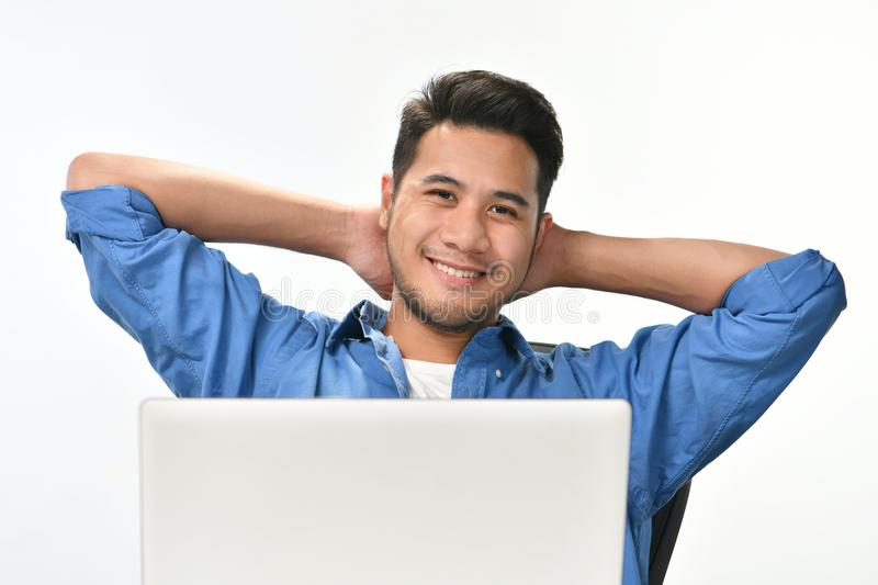 Startup business man sitting in relaxed posture after having work done easily. Casually-dressed startup business man sitting in relaxed posture after having work stock photos