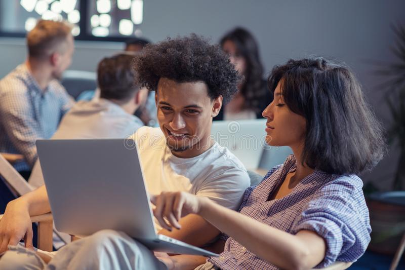 Startup business and new mobile technology concept with young multiethnic couple in modern bright office interior royalty free stock image