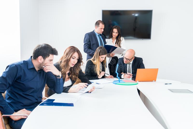 Startup business team on meeting in modern bright office interior mrainstorming. Working on laptop, tablet and with papers. royalty free stock photography