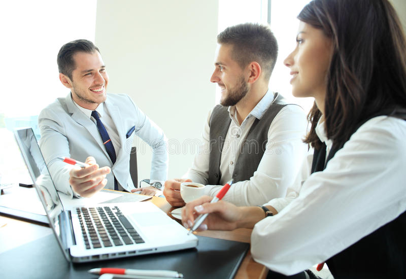 Startup business team on meeting in modern bright office interior brainstorming, working on laptop and tablet computer. royalty free stock photos