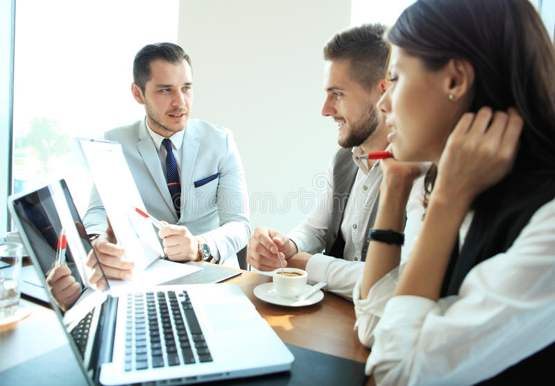 Startup business team on meeting in modern bright office interior brainstorming, working on laptop and tablet computer. royalty free stock photo