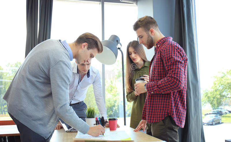 Startup business team on meeting in modern bright office interior brainstorming, working on laptop and tablet computer. stock photos