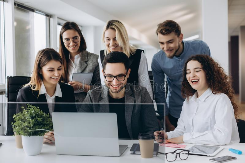 Startup business team on meeting in modern bright office interior smiling and working on laptop stock photography