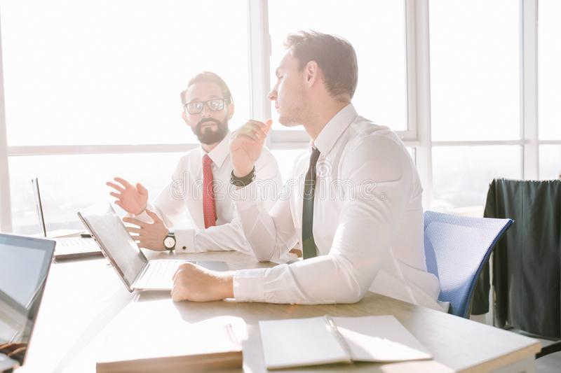Startup diversity teamwork. Two handsome managers in white t-shirts discussing project data while sitting at desk stock image
