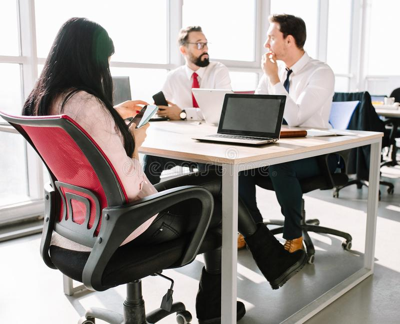 Startup diversity teamwork. Two male managers sitting at desk and discussing project details. Female manager typing message on smartphone royalty free stock photo