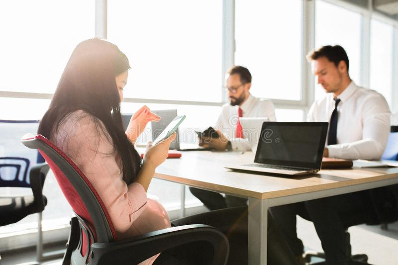 Startup diversity teamwork. Two male and one female managers sitting at desks. Working on laptop and smartphone. Office concept stock image